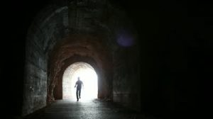 stock-footage-man-runs-into-the-dark-concrete-tunnel-from-the-glowing-end